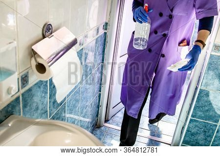 Janitor Cleaning Lady Cleaning, Disinfecting Bathroom In The Office Building. Corona Virus Concept