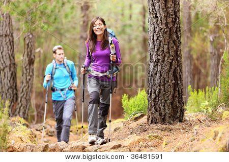 Wanderer im Wald. Paar im Herbst Wald wandern. Asiatische Frau Wanderer vor glücklich lächelnd. Foto von