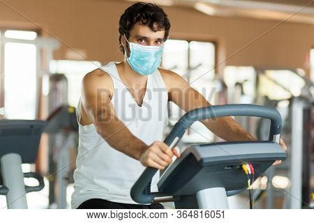 Man in the gym, exercising his legs doing cardio training on bicycle wearing a mask, coronavirus concept