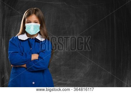Masked girl at school in front of the classroom blackboard