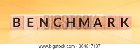 Benchmark Word On A Wooden Cubes On Yellow Background
