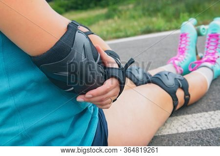 Woman rollerskater with elbow protector pads on her hand and wearing wrist guards