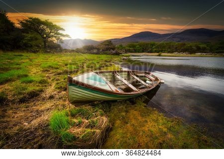 Beautiful scenery of the Killarney lake with boat at sunset in county Kerry, Ireland