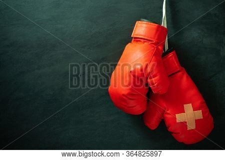 Red Boxing Gloves Hung On Black Cement Wall In Darkness With Lighting. Adhesive Plaster Across Each