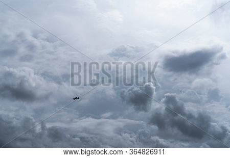 Small Plane In Cloudy Sky For Rainmaking. White Fluffy Clouds With Small Aircraft To Make Artificial