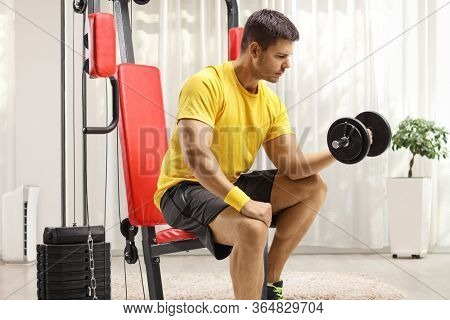 Man sitting on a fitness machine and exercising with a dumbbell at home gym