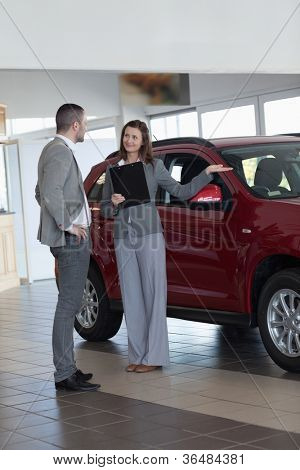 Businesswoman showing a car in a dealership