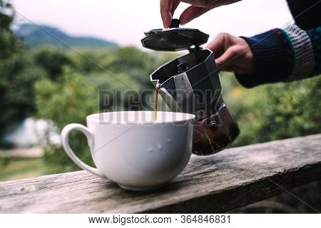 A Woman Pours Coffee Into A White Cup From A Geyser Coffee Maker, Morning Hot Drink In Nature, Girl