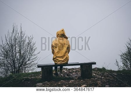 Sad Depressed Woman Sitting On Bench In Raincoat. Rear View Of Depressed Woman. Woman In Depression.