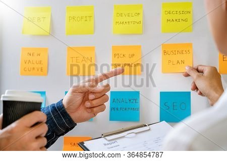 Young Business Workers Posting With Sticky Notes Stickers Reminders  Creative Brainstorming At Board