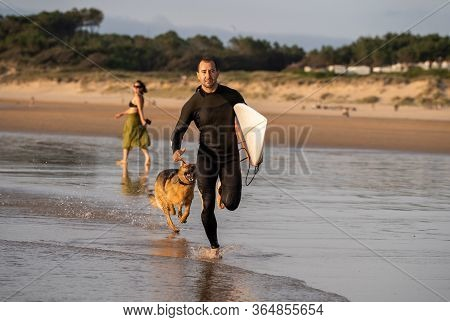 Surfer Having Fun With Best Friend German Shepherd Running And Playing On Dog-friendly Beach At Suns