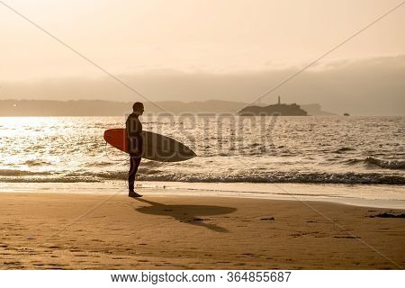 Surfer Walking With Surfboard On The Beach At Sunset Or Sunrise. Vacation And Adventure Lifestyle