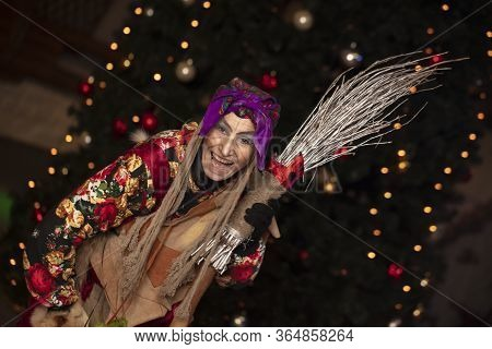 Baba Yaga With A Broom On The Background Of The Christmas Tree.russian Witch.