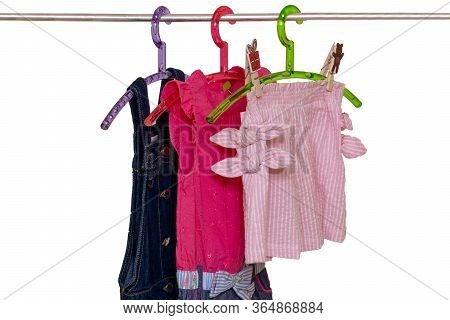 Girls Clothes On Rack. Close-up Of Colorful Stylish Summer Dresses And A Short Pants For The Little