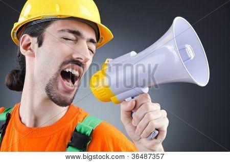 Construction worker with loudspeaker in studio