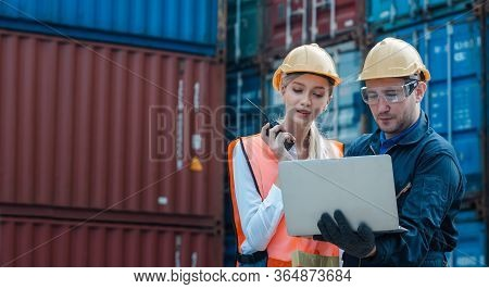 Technician Or Engineer With Yellow Helmet Use Walkie-talkie To Contact With Co-worker In Cargo Conta