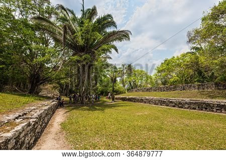 Kohunlich, Mexico - April 25, 2019: A Group Of Tourists Visiting The Stadium Of The Ancient Mayan Ci