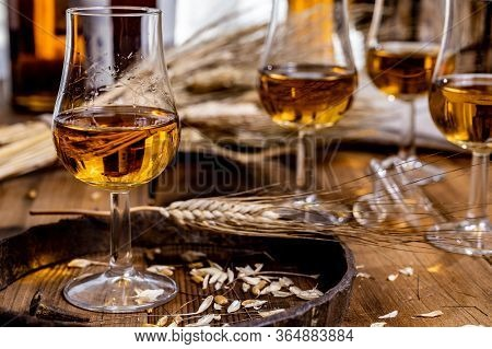 Tasting Glasses With Aged Scotch Whisky Or American Bourbon On Old Dark Wooden Vintage Table With Ba