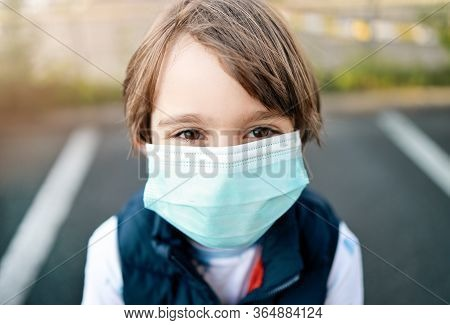 Little Boy Wearing Medical Mask During Coronavirus Covid-19 Pandemic. Close-up And Eye-contact With