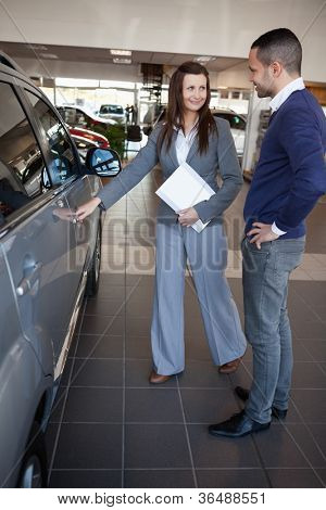 Woman holding car handle in a dealership