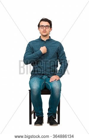 Full Length Portrait Of Perplexed Businessman, Seated On A Chair  Points Index Finger To Himself, Lo