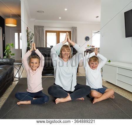 Covid-19 Outrbreak. Family Doing Yoga Together At Home During Coronavirus Quarantine