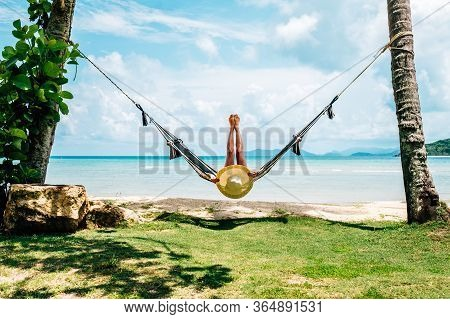 Summer Vacations Concept. Happy Woman In Black Bikini Relaxing In Hammock On Tropical Beach