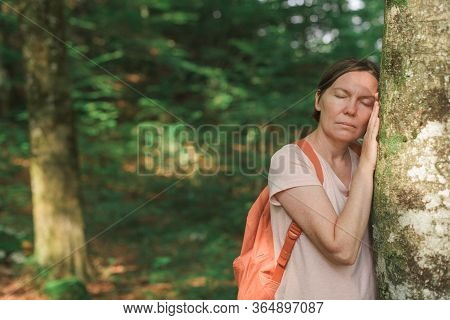 Female Environmentalist Leaning On Tree Trunk In Forest, Selective Focus