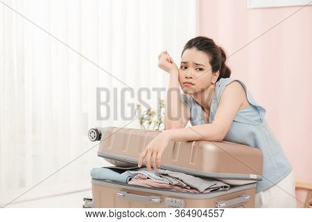 Sad Young Woman Sitting On Stuffed Suitcase, Smiling. Girl Packing Bag For Travel, Closing Hardly Ov