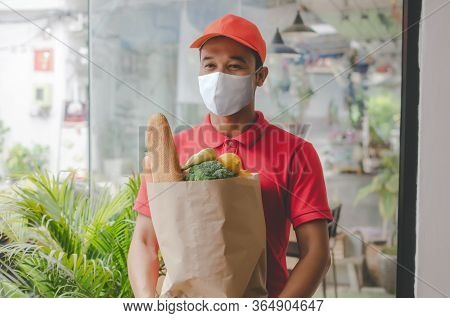 Food Delivery Service Man With Protection Face Mask In Red Uniform Holding Fresh Food Set Bag Waitin
