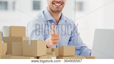 Mid section of a happy Caucasian man using laptop computer at home shopping on line, showing thumbs up with pile of cardboard parcel boxes next to her. Online shopping ecommerce social distancing and