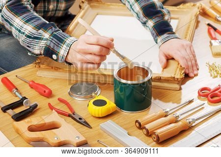 Decorator Varnishing A Wooden Frame