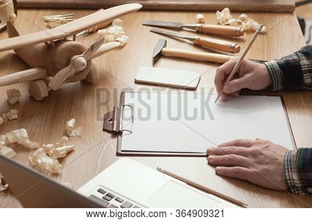 Craftsman Designing A Diy Project On A Clipboard