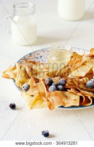 Homemade Thin Pancakes With Berries, Honey And Milk For Breakfast On A Light Background. Traditional
