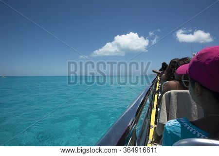 Happy Tourists On Vacation On The Ferry To Isla Mujeres Mexico. The Transparent And Turquoise Caribb