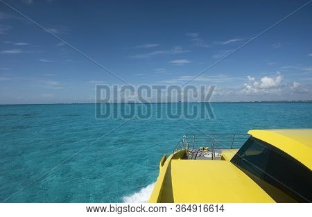 Yellow And Blue Ferry To Isla Mujeres Mexico. In The Background The Turquoise Caribbean Sea And The