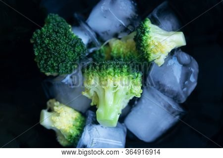 Freshly cooked vegetables - broccoli lie on ice in a black plate. The principle of cooking vegetable