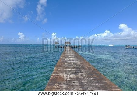 Long Wooden Pier Extends Over The Caribbean Sea To Isla Mujeres Mexico. Travel And Nature Concept