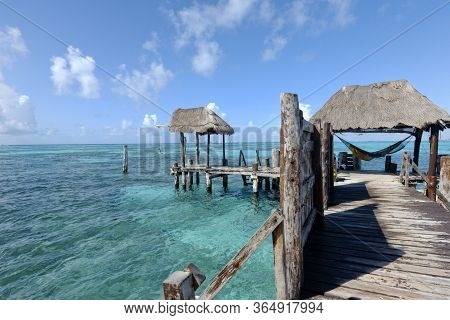Young Happy Man Relaxing In A Hammock Looking At The Sea At The End Of A Wooden Pier On The Caribbea