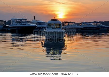 Stunning View Of Yachts At The Pier Against The Sunset. Yachts And Boats Anchored In Marina. A Motor