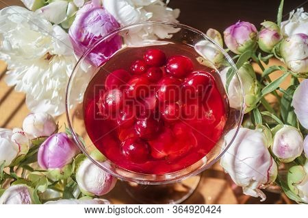 Magic Solemn Still Life With Glass Of Red Drink With Autumn Organic Berries Surrounded By White Flow