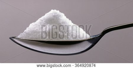 Salt portion on teaspoon macro photography.