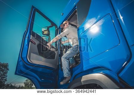 Caucasian Male Truck Driver Stepping Out Of Vehicle At Rest Stop.