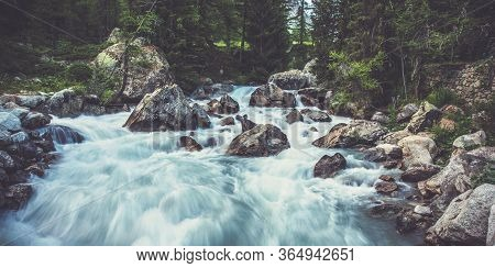 View Of Robust Water Flow In Small Stream With Boulders Trees And Forest Landscape.