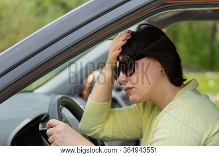 The Woman Behind The Wheel Of A Car Suffering From Psychological Stress And Moral Fatigue. Exhausted
