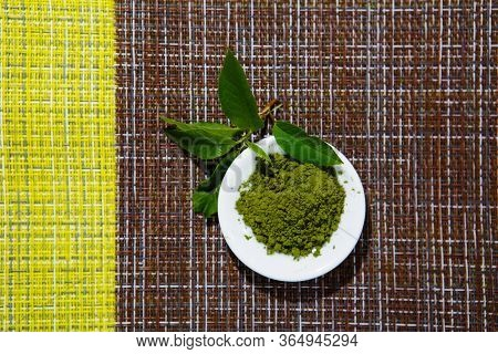Japanese Green Tea Matcha Powder On A White Saucer On A Brown Background Combined With Green, With A