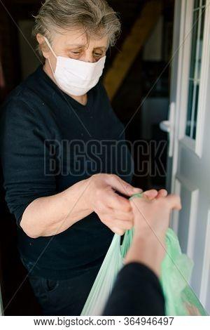 Person Bringing Food, Groceries To An Elderly Woman In Quarantine. Corona Virus Outbreak