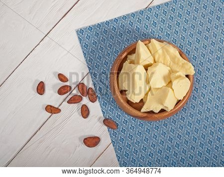 Pieces Of Natural Cocoa Butter In Bowl With Cocoa Beans. Top View. Macro Photo