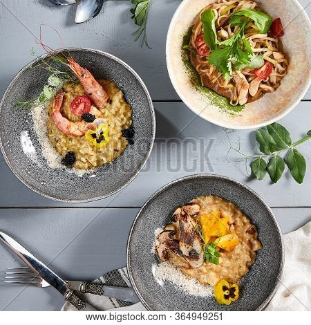 Risotto and noodles in ceramic bowls top view. Rise dishes with meat and seafood, pasta with chicken. Delicious delicatessens, served italian and asian cuisine meals, restaurant eating