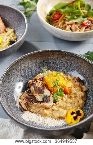 Risotto with white mushrooms and pumpkin in gray bowl. Italian rice porridge close up. Delicious traditional food with violet flowers and greenery decoration. Served restaurant meal, delicatessen